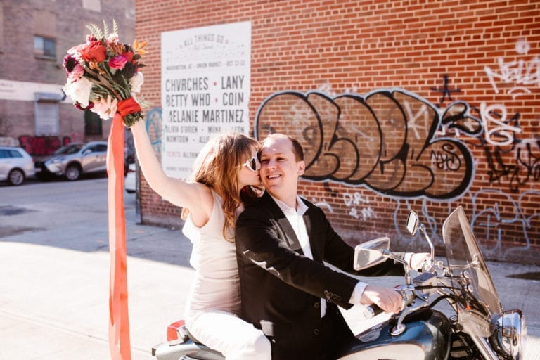 Couple on motorcycle throwing flowers